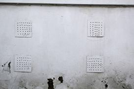 white-wall-with-ventilation-holes-covered-with-metal-plates